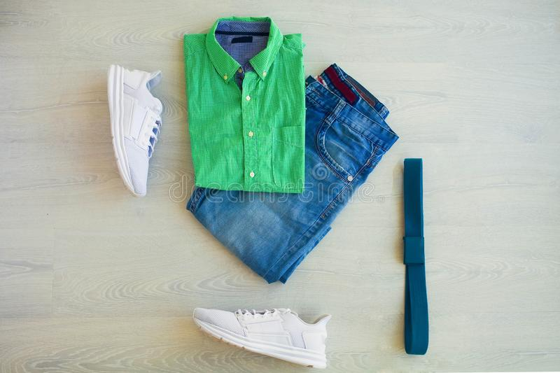 Green plaid shirt, jeans shorts and white sneakers on a white background, men`s wear. stock photos