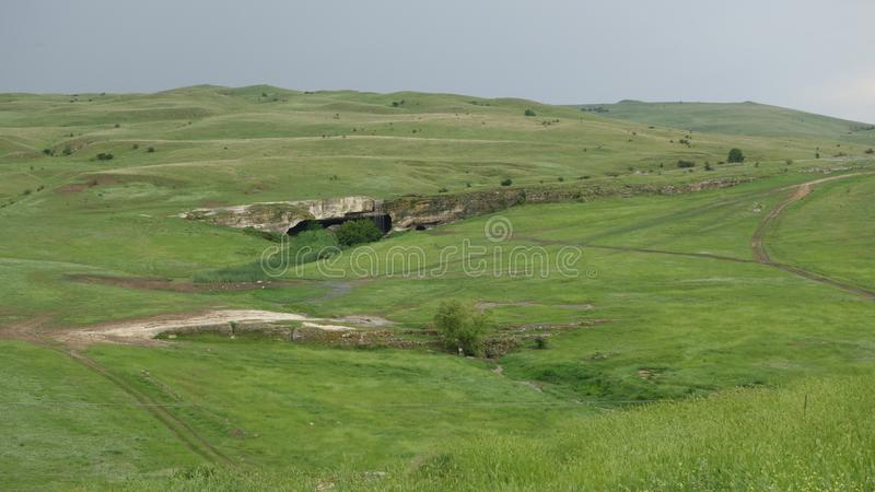 Green plain with cave. And small hills royalty free stock image