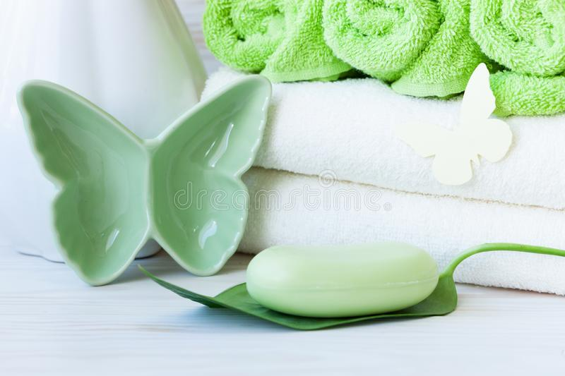 Green plant leaf,  butterfly figurines, green soap, vase and towels. Concept for spa, beauty and health salons. Close up photo on. White wooden background stock photos