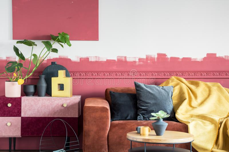 Green plant in white pot next to black and gold vases on pastel pink and burgundy shelf in living room with ombre wall and brown royalty free stock photography