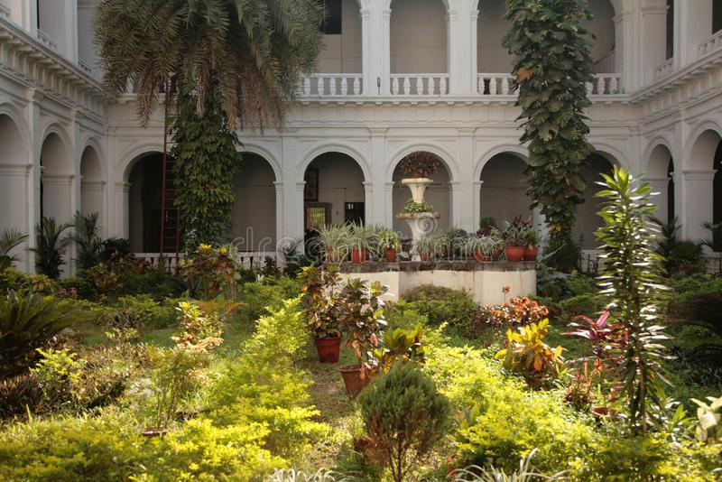Green plants in the courtyard of an apartment house. Of colonial style. India stock photos