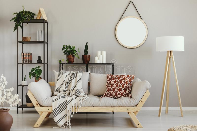Green plants in pots, candles and books on metal shelves in beige scandinavian living room. With comfortable settee, lamp and mirror on the wall stock photos