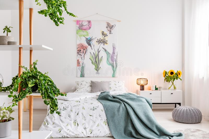 Green plants on shelves beside a bed dressed in white cotton bedding and teal blue blanket in a bright bedroom interior stock photography