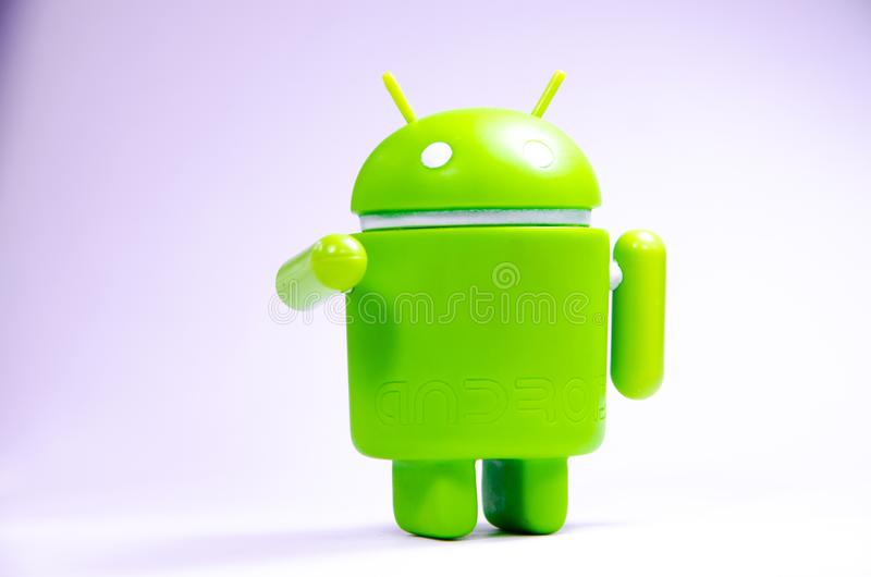 Green plastic Android figure on a white background and with a smartphone stock photography