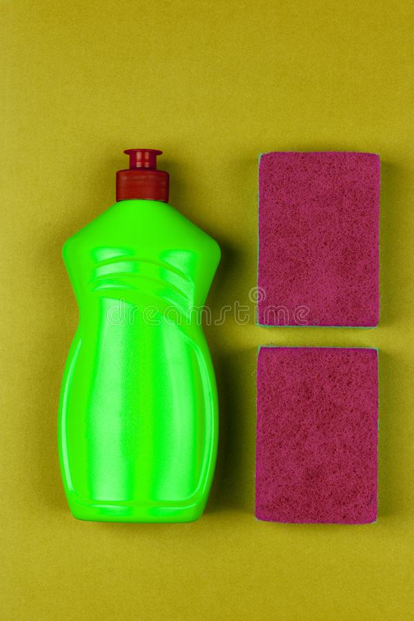 Green plastic bottle of dishwashing liquid and red sponge on greenish-yellow background close-up top view,. Flat lay stock images
