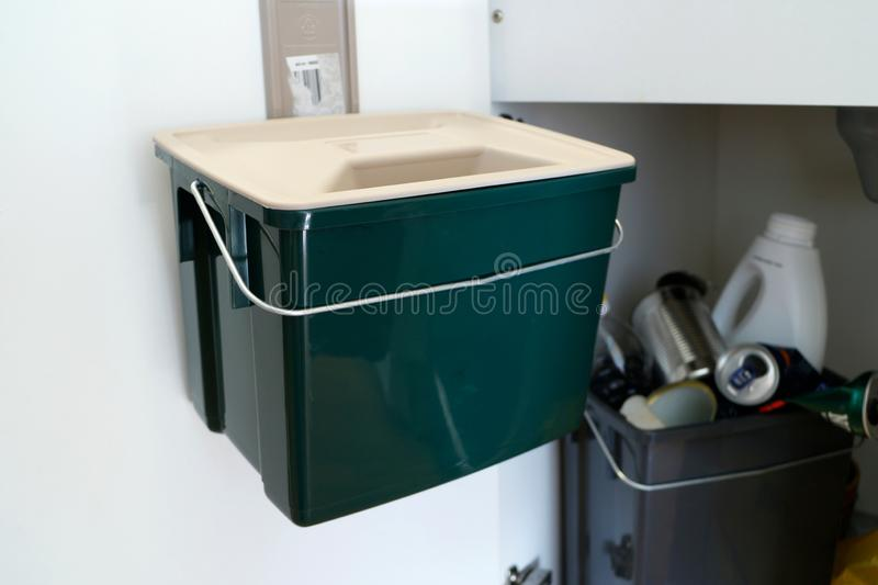 Green Plastic container for food waste/scraps. Trash cabinet inside a kitchen. Recycling/Composting royalty free stock photography