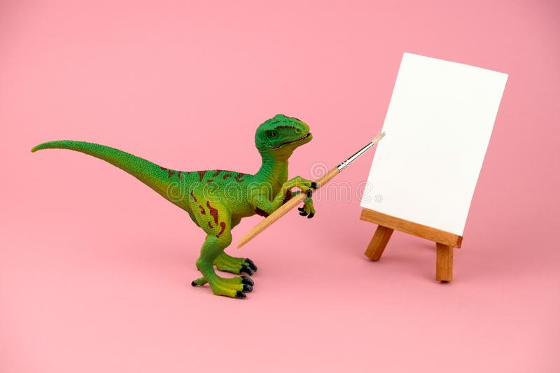 Plastic dinosaur toy holding artistic brush and standing near mock up canvas, creative conceptual still life on a pink. Green plastic dinosaur toy holding royalty free stock photo