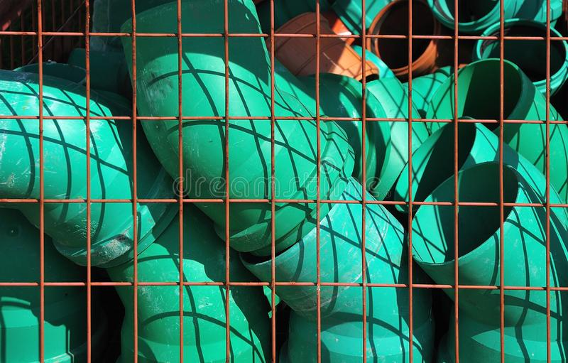 Green plastic elbow pipes for sewer lines in a metal cage royalty free stock photos
