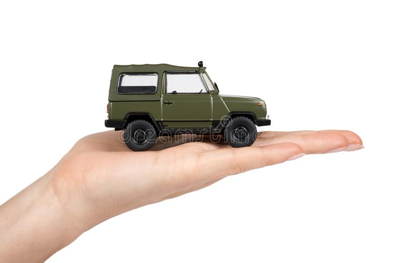 Green plastic toy SUV vehicle, offroad truck, military car, 4x4 auto in hand. Isolated on white background.  royalty free stock photography