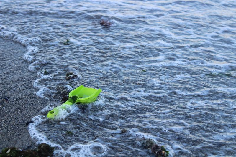 Green plastic toy in the wave stock photography