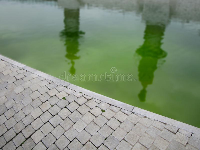 Green pond water along paved tiled road with reflections royalty free stock photo