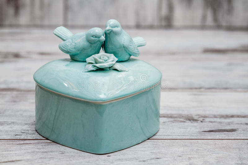 Green Porcelain Box with Birds and Flowers. On white wooden background royalty free stock photography