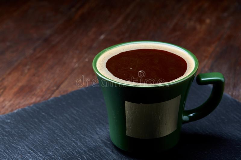 Green porcelain coffee cup on stone board over wooden background, selective focus, close-up royalty free stock photo