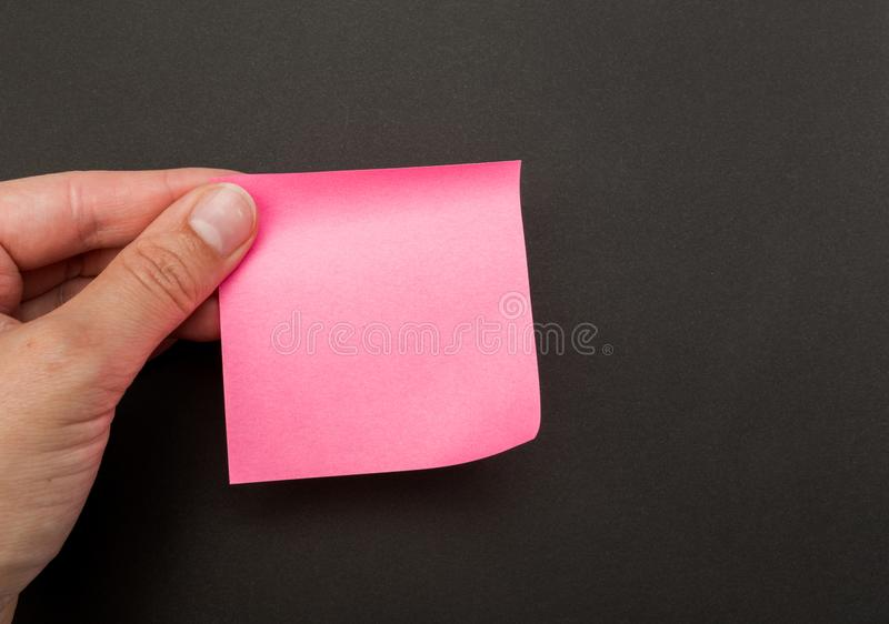 Green post-it note with hand on black background. Image royalty free stock image