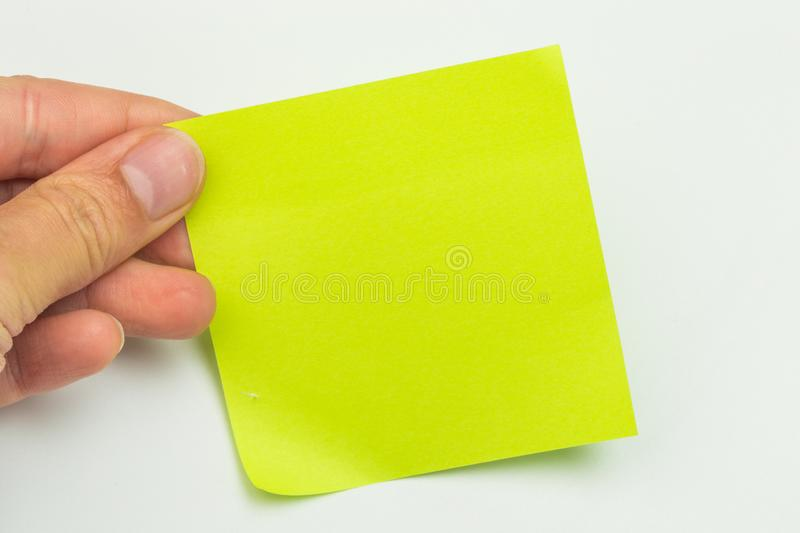 Green post-it note with hand on white background. Image stock photography