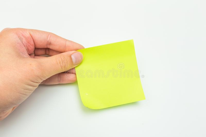 Green post-it note with hand on white background. Image royalty free stock photo