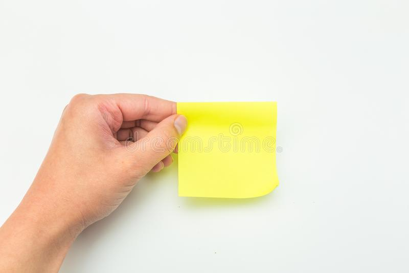 Green post-it note with hand on white background. Image royalty free stock photography
