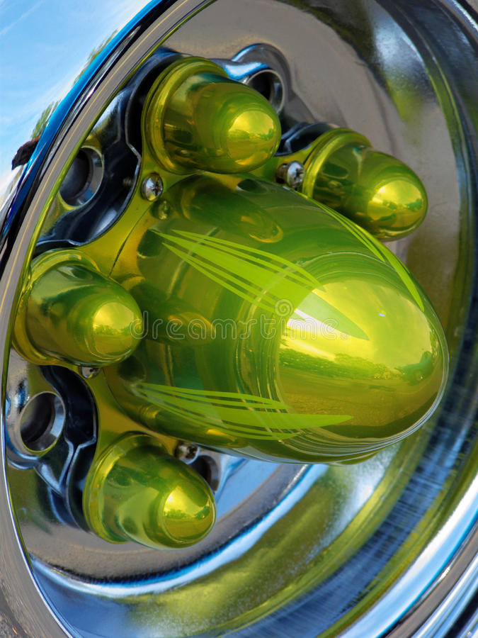 Green Protrusions. Chrome hub and wheel of restored old timey automobile stock images