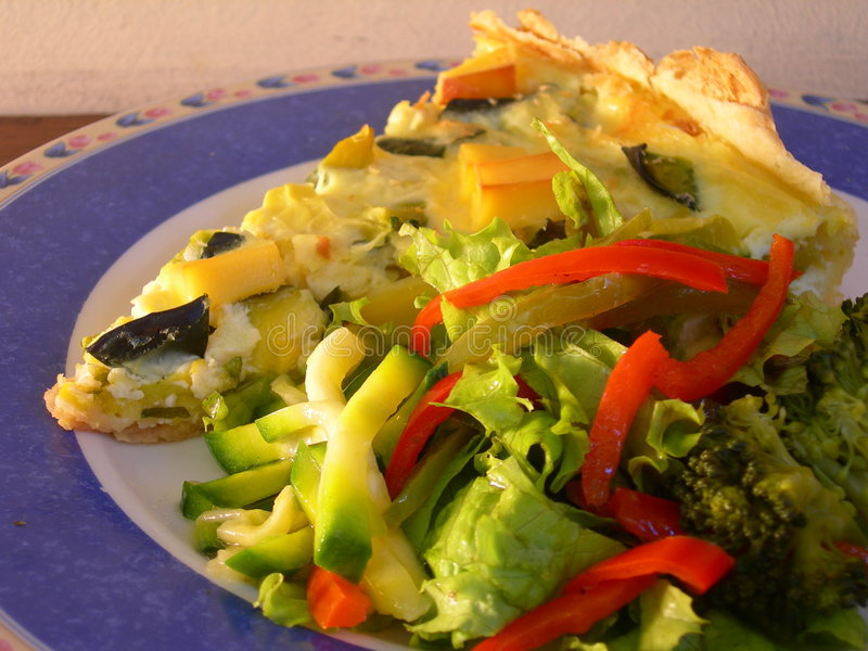 Green pumpkin pie. With vegetarian salad in a restaurant table stock image