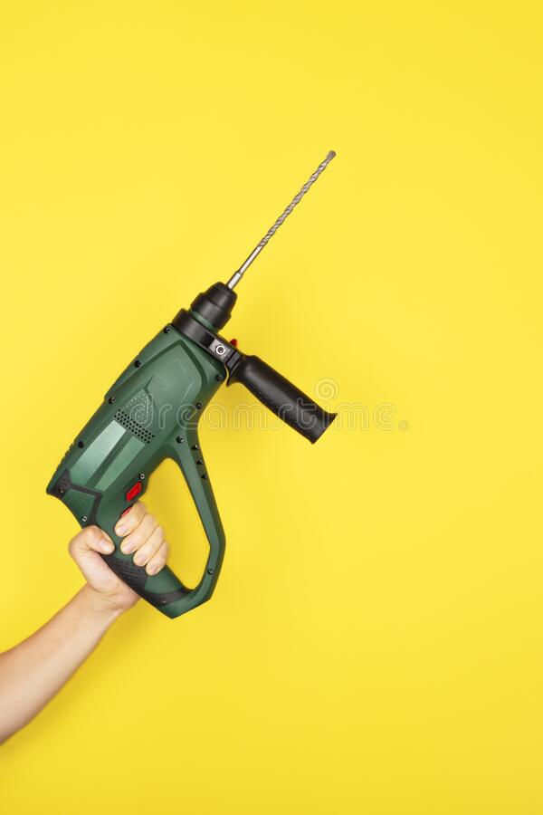 Green Puncher in the hands of a builder stock photo