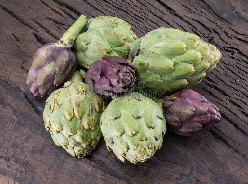 Green and purple artichoke flower edible buds on wooden background royalty free stock photos