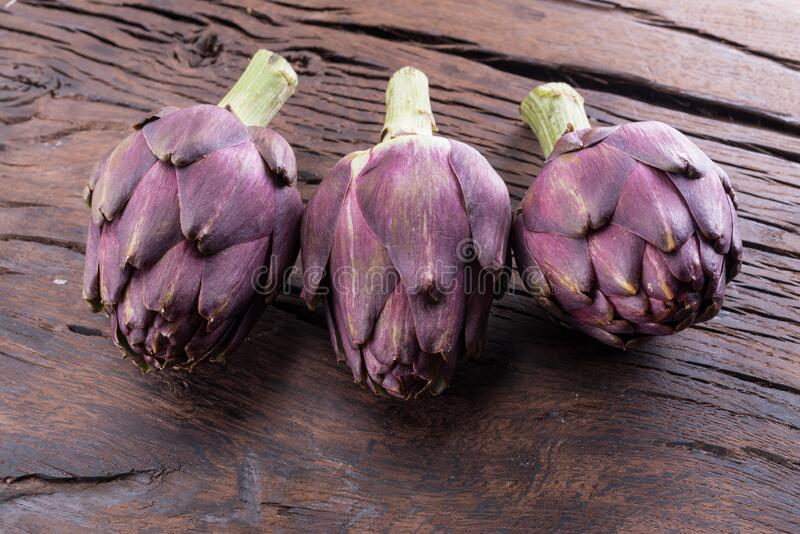 Green and purple artichoke flower edible buds on wooden background royalty free stock photo