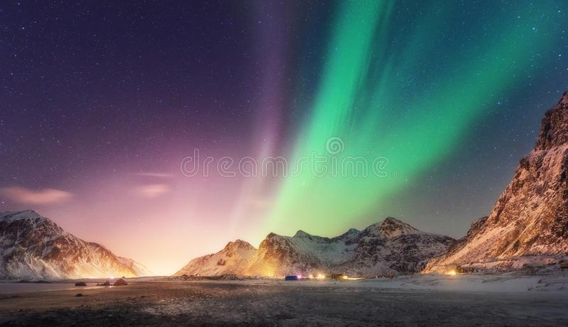 Green and purple aurora borealis over snowy mountains stock photo