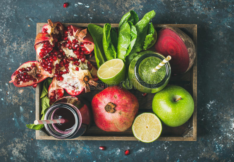 Green, purple fresh juices with fruit, greens, vegetables in tray stock photography