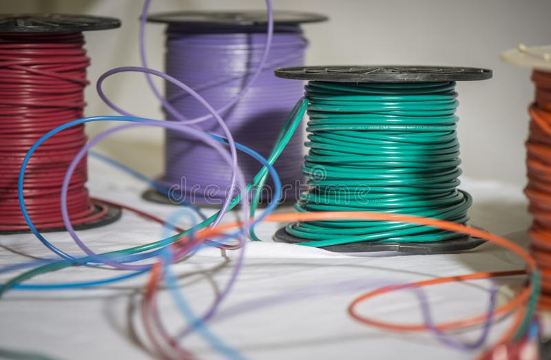 Green purple red spools of wire. Colorful spools of wire in electronics manufacturing plant used in computer hardware assembly stock photos
