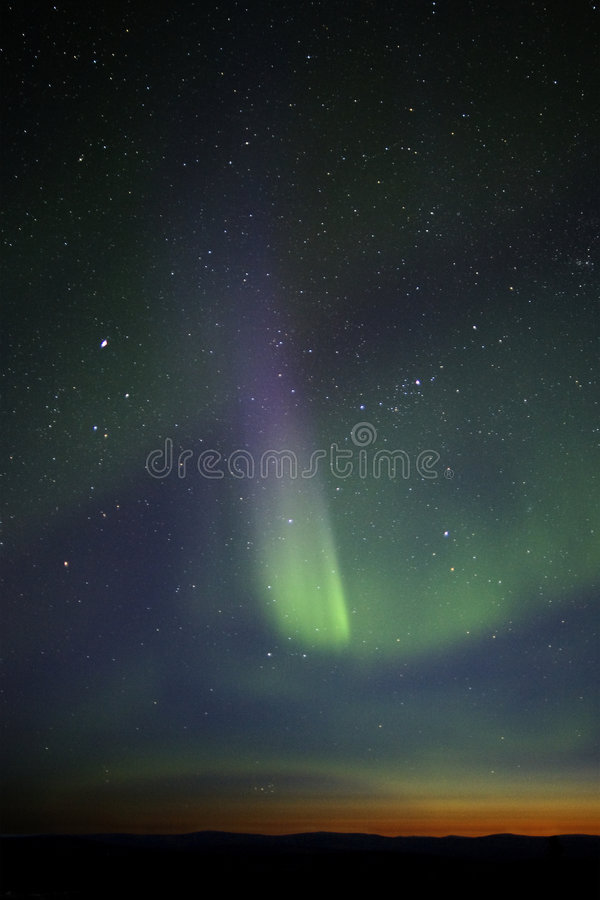 Green-purple streak of aurora over twilight horizon. Many stars royalty free stock photo