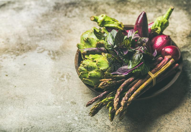 Flat-lay of green and purple vegetables on plate, concrete background royalty free stock photography