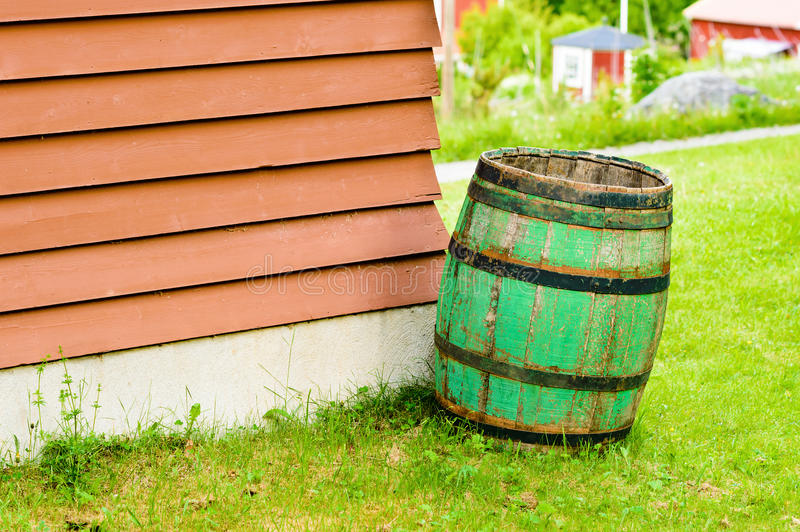 Green rain barrel. Green wooden barrel to collect rain water in. Slightly tilted and with small red cabins in background royalty free stock photo
