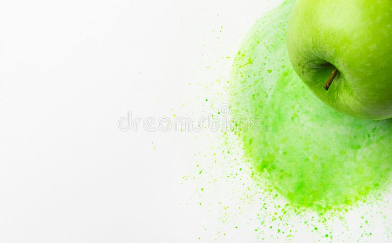Green raw apple on hand drawn watercolor background of chartreuse yellow color mixture splashes paintbrush strokes. Mixed media. Green raw apple on hand drawn royalty free stock image