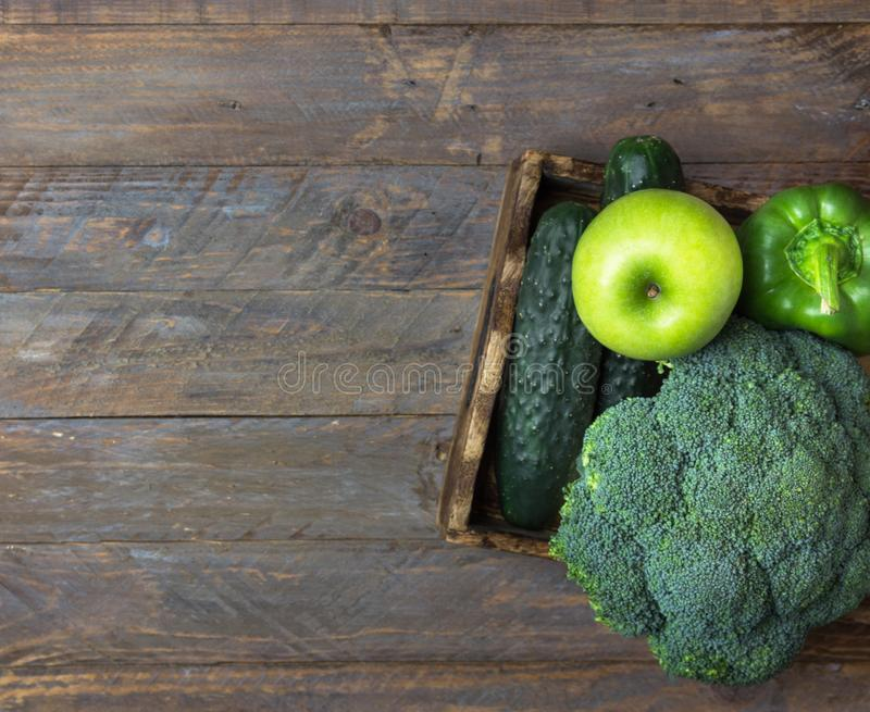 Green raw organic vegetables fruits broccoli cucumbers bell peppers apples in box on wooden table. Healthy diet dietary fiber royalty free stock images