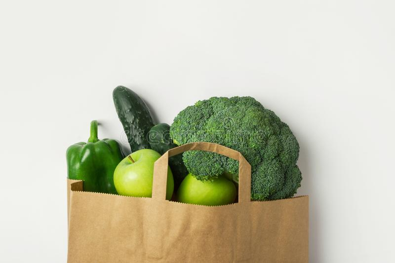 Green raw organic vegetables fruits broccoli cucumbers bell peppers apples in brown Kraft paper grocery bag on white background royalty free stock photo
