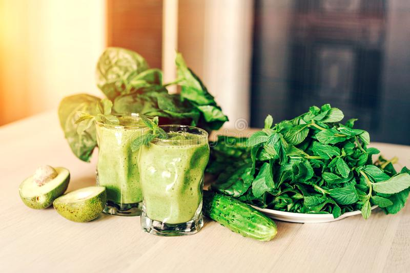 Green ready-made smoothies in glasses, avocado halves and mint leaves, tops of beetroot and spinach on the table stock photo