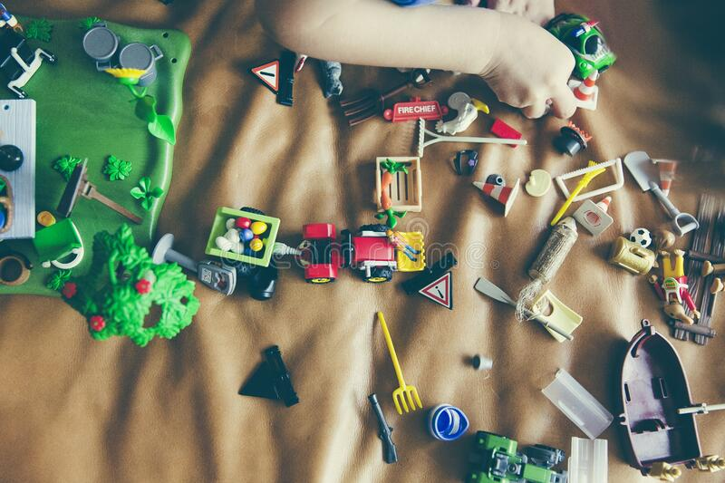Green Rectangular Toy, Gray Boat Toy, Gray Shovel Toy, and Green Car Toy on Top of Brown Leather Surface stock images