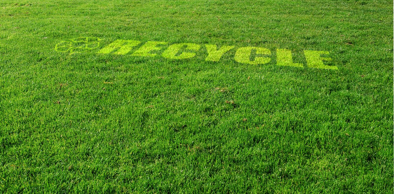 Green Recycling. Recycle Symbol on Green Lawn royalty free stock image