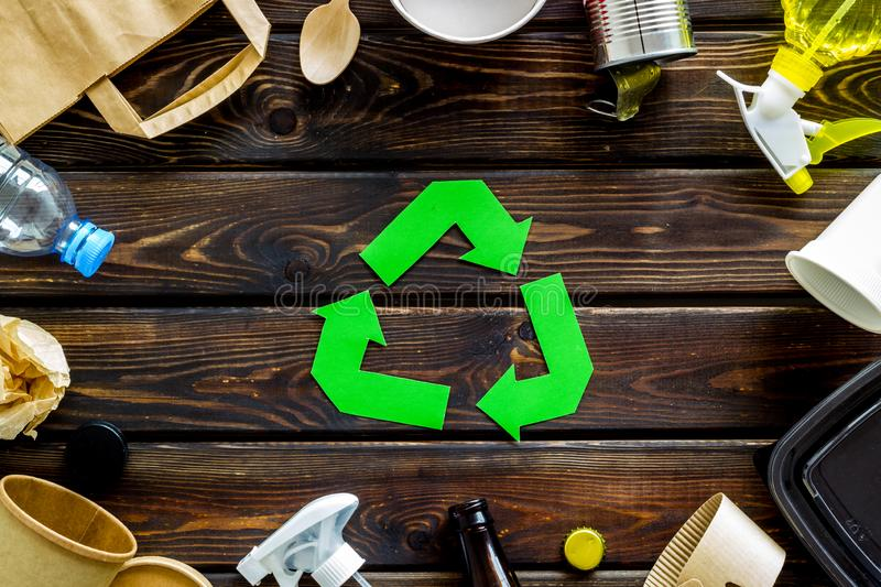 Recycling symbol and different garbage, paper bag, cup, flatware, plastic bottle for ecology wooden background top view royalty free stock photo