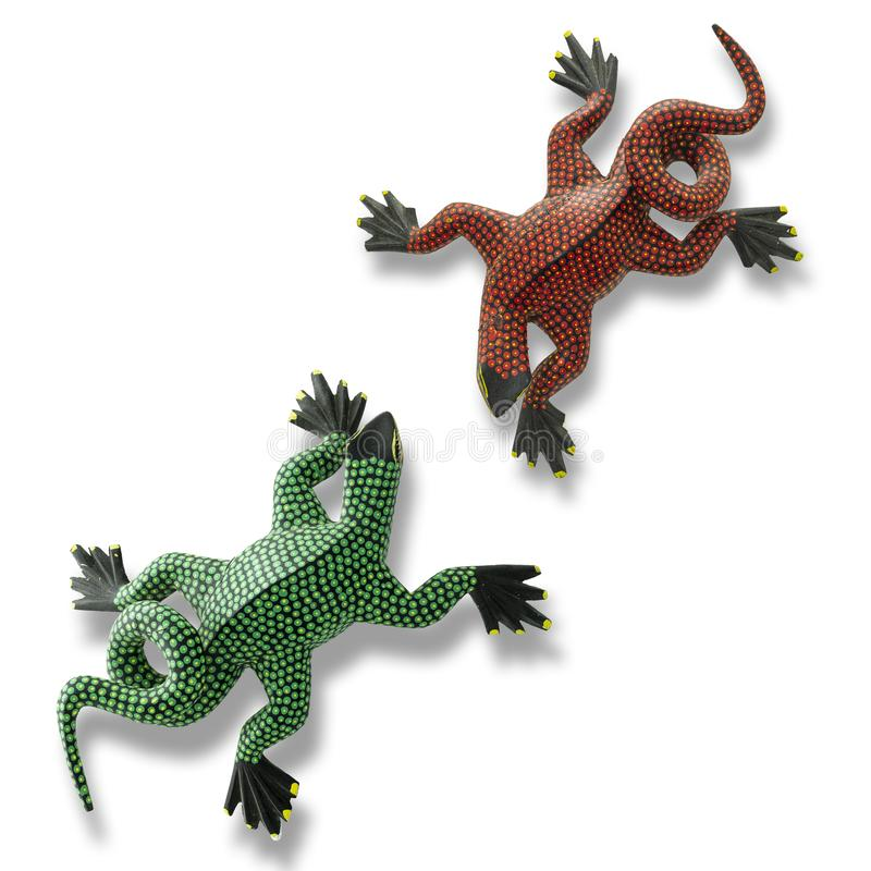 Two handmade Alebrijes in the state of Oaxaca on white background. Green and red alebrijes handmade crafts from San Martin Tilcajete in the state of Oaxaca royalty free stock photo