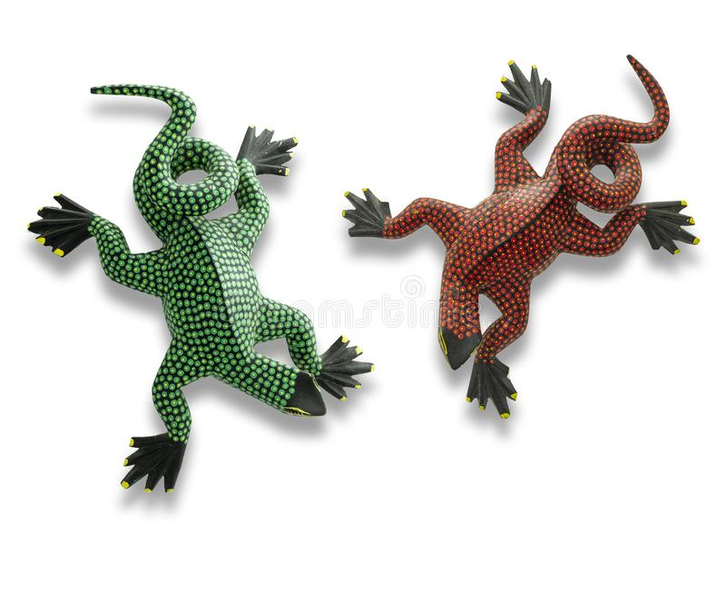 Two handmade Alebrijes in the state of Oaxaca on white background. Green and red alebrijes handmade crafts from San Martin Tilcajete in the state of Oaxaca stock images