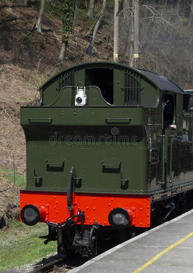 Green and red back of steam train engine moving next to platform. Green and red back of vintage steam train engine moving next to grey platform with trees and royalty free stock images