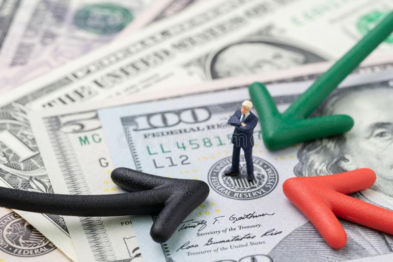 Green, red and black arrow pointing to businessman standing on US Federal Reserve emblem on hundred dollars banknote as FED stock photos