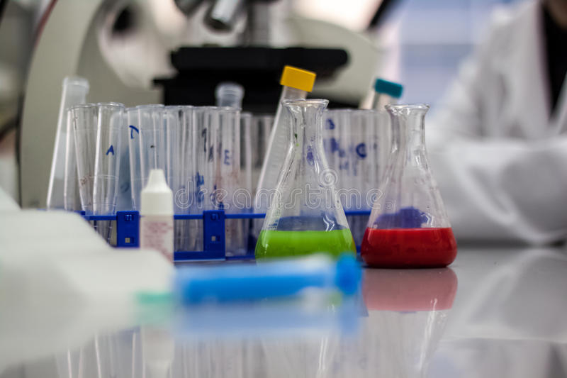 Green and red chemical compounds microscope and test tubes in bi. Otechnology laboratories stock photos