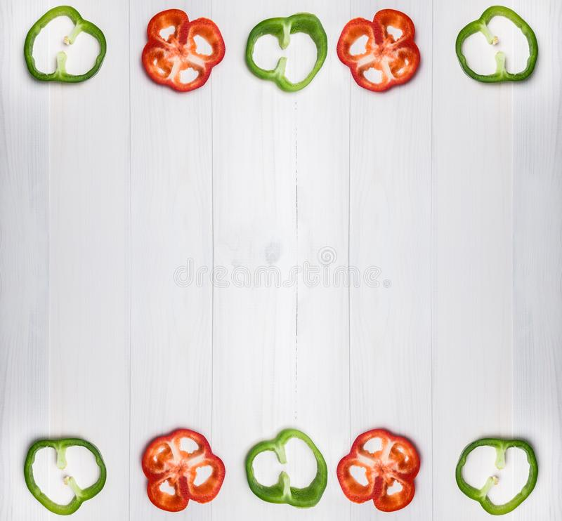 Green and red fresh bell pepper or capsicum cut into thin slices isolated on white background stock images