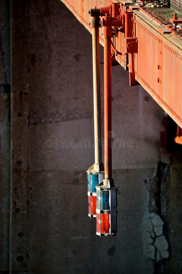 Green and red glass signal lights suspended under the metal girders of a bridge. Control the flow of traffic on a river stock photography