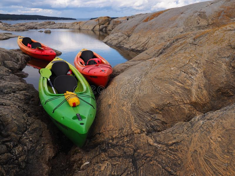 Green and red kayaks moored between rocks stock images