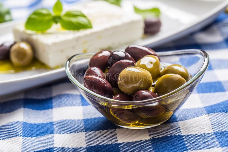 Green and red olives in bowl with olive oil and greek feta cheese in the background royalty free stock photography
