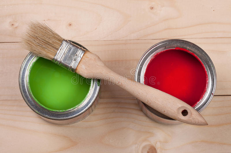 Green and red paint in the bank to repair and brush on the light wooden background royalty free stock images