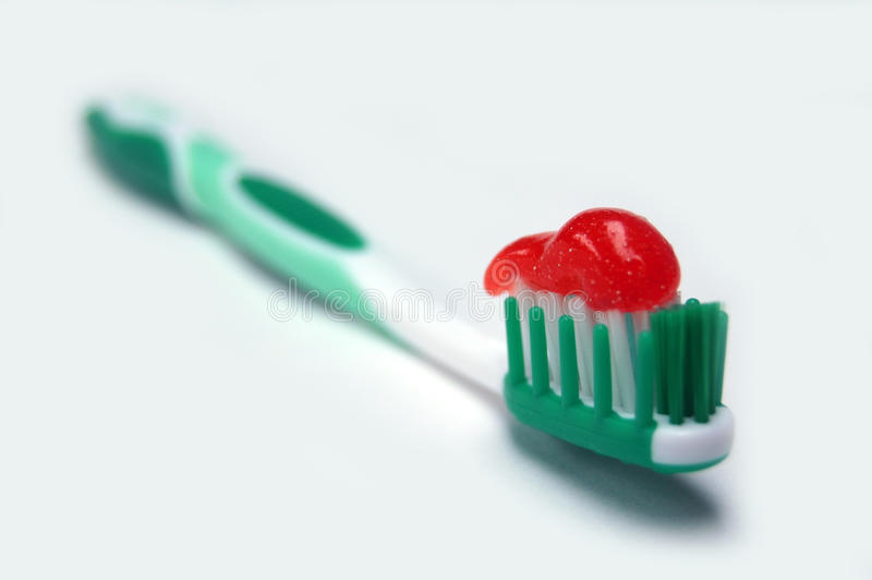Green with red paste. Close up of green toothbrush with red paste stock images